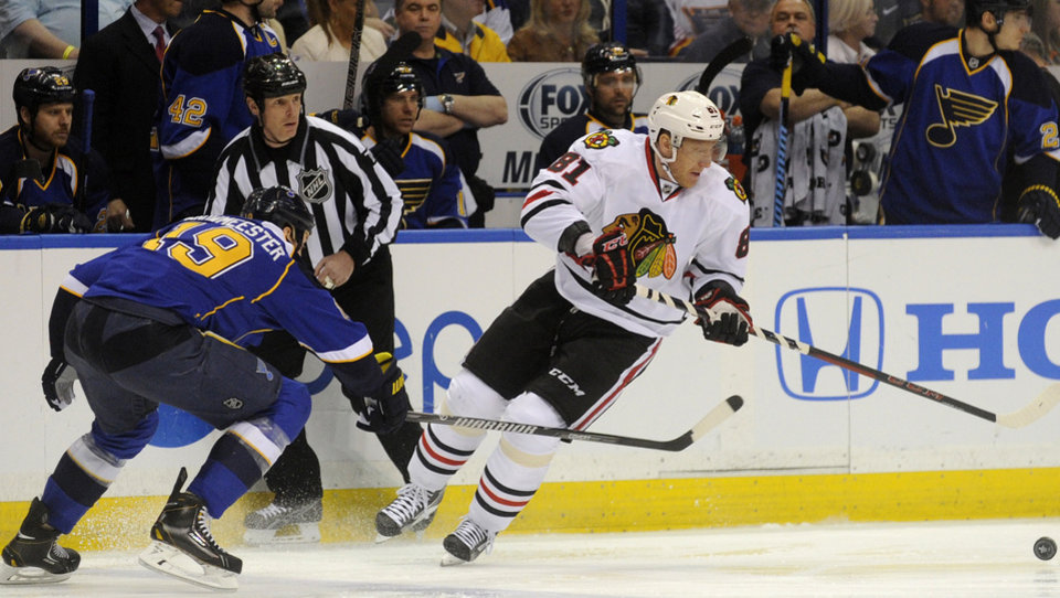 Photo - Chicago Blackhawks' Marian Hossa (81), of Sweden, and St. Louis Blues' Jay Bouwmeester (19) reach for a loose puck during the first period in Game 2 of a first-round NHL hockey playoff series on Saturday, April 19, 2014, in St. Louis. (AP Photo/Bill Boyce)
