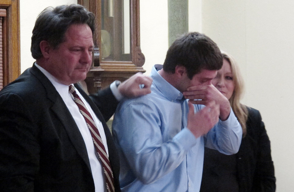 Photo - Former University of Montana quarterback, Jordan Johnson, center, reacts after being acquitted of rape charges during his trial Friday March 1, 2013 in Missoula, Mont. With Johnson are his attorneys, David Paoli and Kirsten Pabst. The accusations against Johnson, 20, have drawn much attention in Montana, where UM football is the top sports attraction. Jurors deliberated for less than two hours. (AP Photo/Matt Gouras)
