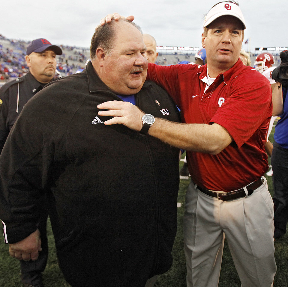 Photo - Kansas coach Mark Mangino and Bob Stoops meet at mid field after the college football game between the University of Oklahoma Sooners (OU) and the University of Kansas Jayhawks (KU) on Saturday, Oct. 24, 2009, in Lawrence, Kan. Oklahoma won the game 35-13. Photo by Chris Landsberger, The Oklahoman