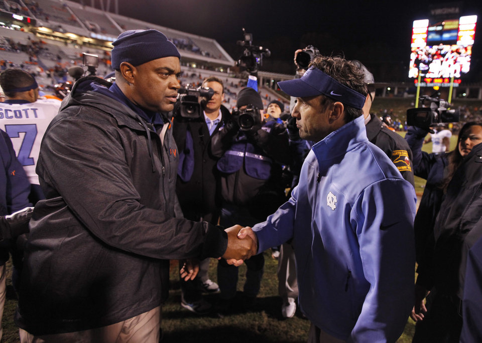 Photo -   Virginia head coach Mike London, left, and North Carolina head coach Larry Fedora shake hands after an NCAA college football game at Scott stadium Thursday, Nov. 15, 2012 in Charlottesville, VA. North Carolina won the game 37-13. (AP Photo/Steve Helber)