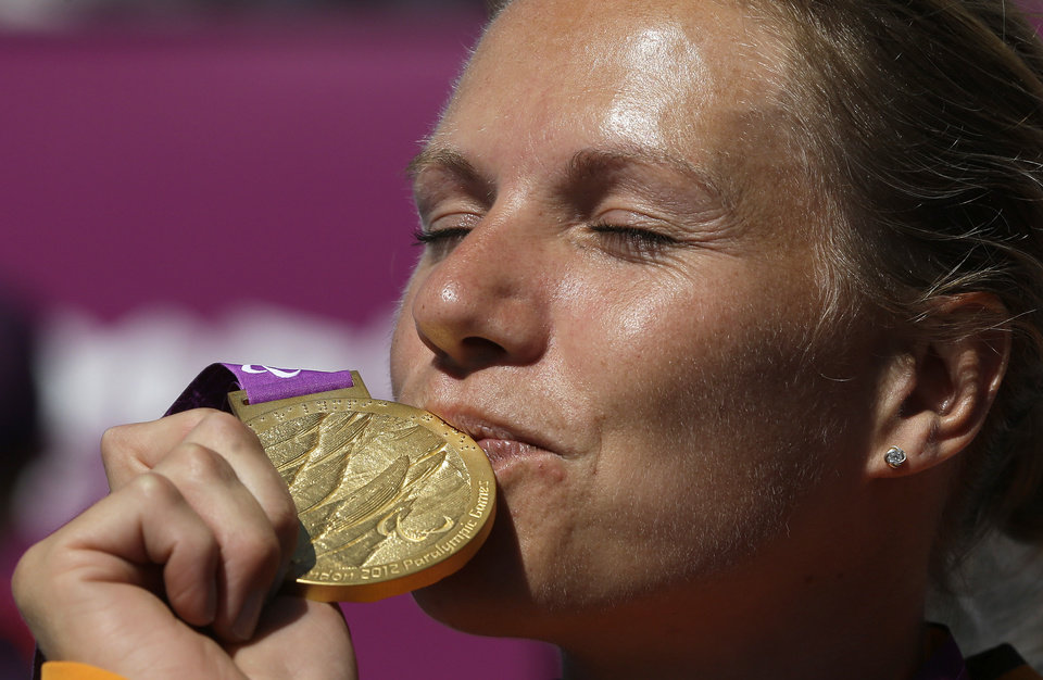 Photo -   Esther Vergeer of the Netherlands kisses her gold medal for winning the women's wheelchair tennis final at the 2012 Paralympics games, Friday, Sept. 7, 2012, in London. Vergeer defeated Aniek Van Koot in the final 6-0, 6-4.(AP Photo/Alastair Grant)