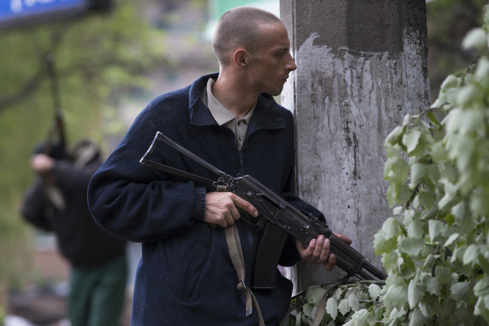 Photo - A Pro-Russian gunman holds a weapon behind barricades in Slovyansk, eastern Ukraine, Friday, May 2, 2014. Ukraine launched what appeared to be its first major assault against pro-Russian forces who have seized government buildings in the country's east, with fighting breaking out Friday in a city that has become the focus of the insurgency. (AP Photo/Alexander Zemlianichenko)