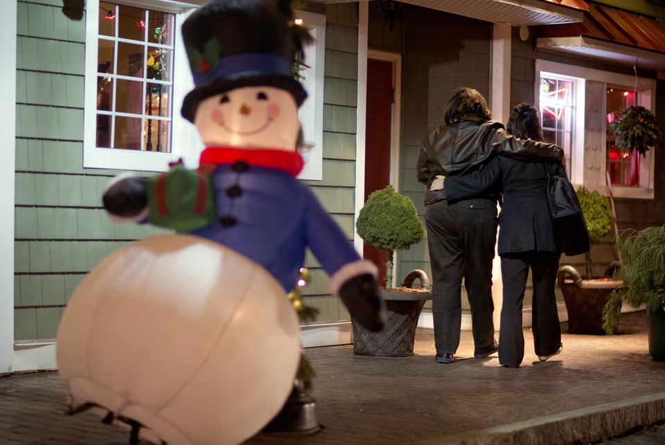 Mourners walk past a Frosty the Snowman Christmas decoration after visiting a memorial for the Sandy Hook Elementary School shooting victims, Dec. 19, 2012, in Newtown, Conn. (AP Photo/David Goldman)