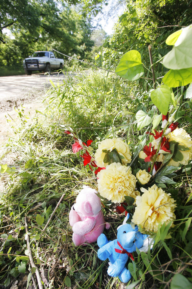 Photo - Pink bear, blue elephant and flowers at the place were Taylor Placker and Skyla Whitaker were shot and killed last Sunday on the dirt road near one of their homes, Tuesday, June 10, 2008.  Photo by David McDaniel /The Oklahoman