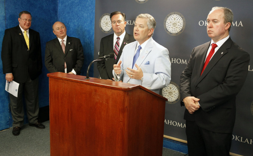 Photo - Insurance Commissioner John Doak speaks to members of the media along with AAA Oklahoma's Chuck Mai, left, Sen. Rick Brinkley, Rep. Todd Russ, and Rep. Marty Quinn, as they unveil insurance legislation during a news conference at the state Capitol in Oklahoma City on Tuesday.  By Paul Hellstern, The Oklahoman  PAUL HELLSTERN