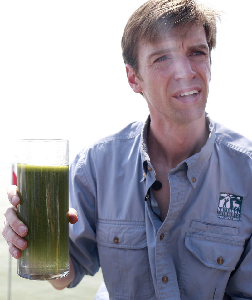 Photo - Collin O'Mara, president and CEO of the National Wildlife Federation, holds a sample glass of water as he talks about algae near the City of Toledo water intake crib, Sunday, Aug. 3, 2014, in Lake Erie, about 2.5 miles off the shore of Curtice, Ohio. More tests are needed to ensure that toxins are out of Toledo's water supply, the mayor said Sunday, instructing the 400,000 people in the region to avoid drinking tap water for a second day. Toledo officials issued the warning early Saturday after tests at one treatment plant showed two sample readings for microcystin above the standard for consumption, possibly because of algae on Lake Erie. (AP Photo/Haraz N. Ghanbari)