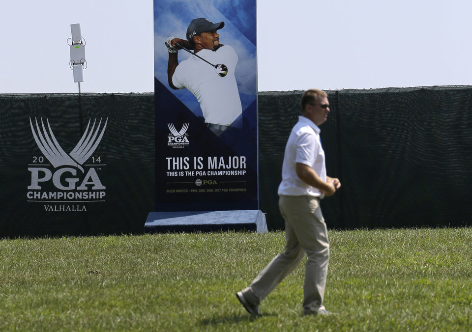 Photo - A man walks past a photo of golfer Tiger Woods at the PGA Championship golf tournament at Valhalla Golf Club Monday, Aug. 4, 2014, in Louisville, Ky. Whether Woods will play in the tournament, which is set to begin on Thursday, is unclear after he suffered a setback Sunday when he was stricken with back pain and withdrew after eight holes from the Bridgestone Invitational. (AP Photo/Jeff Roberson)