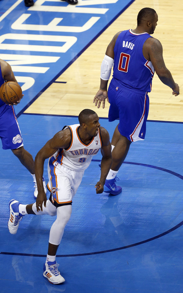 Photo - Oklahoma City's Serge Ibaka (9) celebrates in front of Los Angeles' Glen Davis (0) during Game 2 of the Western Conference semifinals in the NBA playoffs between the Oklahoma City Thunder and the Los Angeles Clippers at Chesapeake Energy Arena in Oklahoma City, Wednesday, May 7, 2014. Photo by Sarah Phipps, The Oklahoman