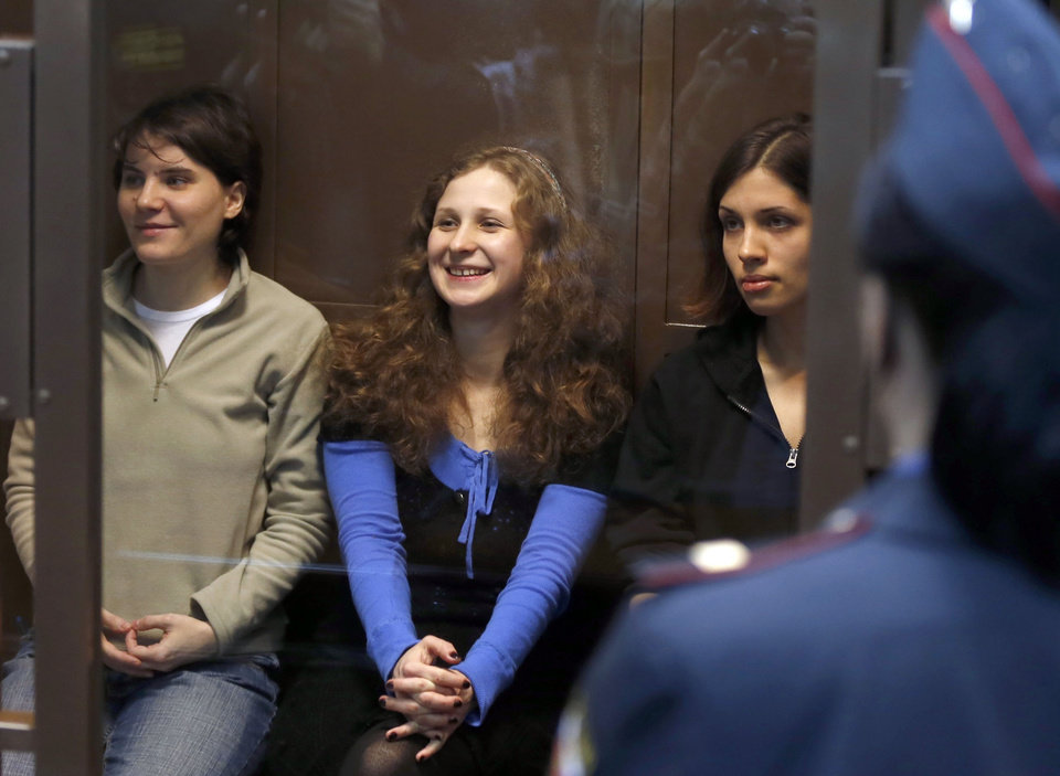 Photo -   CORRECTS LEFT TO RIGHT Feminist punk group Pussy Riot members, from left, Yekaterina Samutsevich, Maria Alekhina, and Nadezhda Tolokonnikova sit in a glass cage at a court room in Moscow, Wednesday. Oct. 10, 2012. Three members of the punk band Pussy Riot are set to make their case before a Russian appeals court that they should not be imprisoned for their irreverent protest against President Vladimir Putin. Their impromptu performance inside Moscow's main cathedral in February came shortly before Putin was elected to a third term. The three women were convicted in August of hooliganism motivated by religious hatred and sentenced to two years in prison. (AP Photo/Sergey Ponomarev)