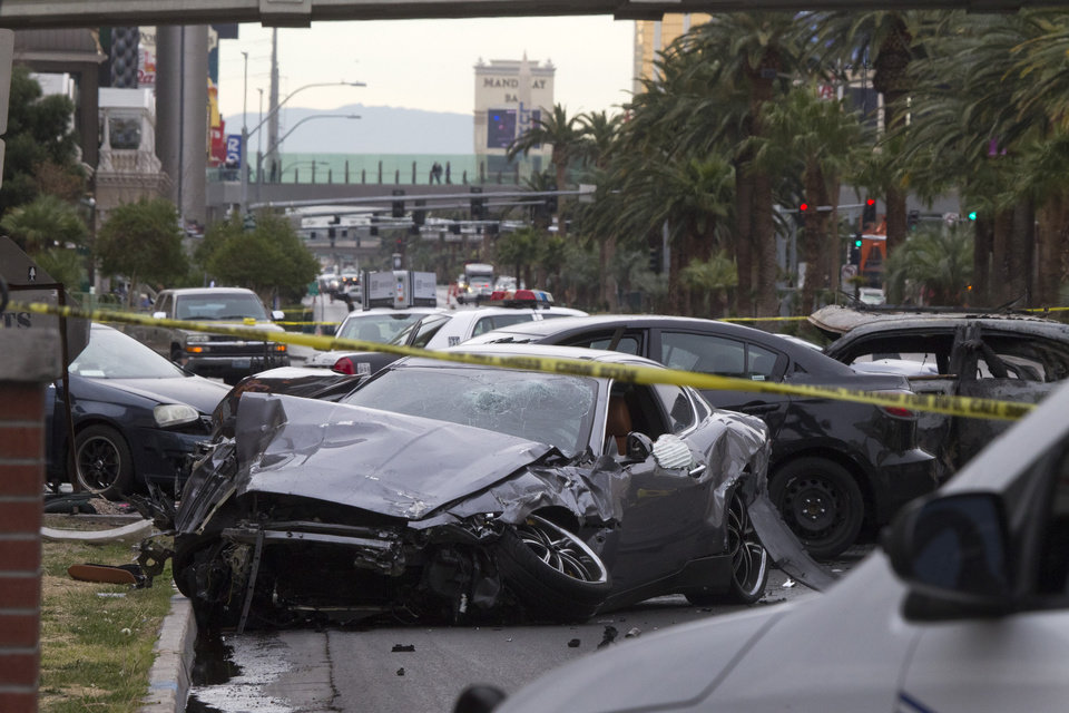 Photo - Police rope off the scene of  a shooting and multi-car accident on the Las Vegas Strip in Las Vegas early Thursday, Feb. 21, 2013.  Authorities say at least one person in a Range Rover shot at people in a Maserati that then crashed into a taxi cab. The taxi cab burst into flames, and the driver and passenger were killed. The male driver of the Maserati also died, and his passenger was shot. (AP Photo/Las Vegas Sun, Steve Marcus)