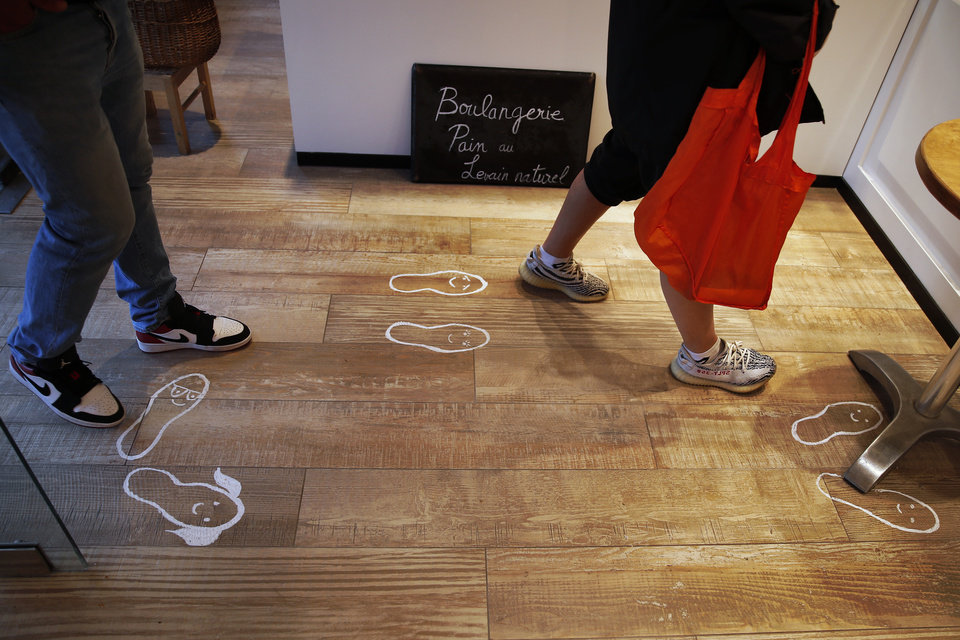 Photo -  Paintings of footprints are displayed for social distancing in a bakery in Paris, Tuesday, March 31, 2020 as the government announced an extension of the initial 15-day home confinement period that came into force on March 17 in a bid to brake the spread of the Covid-19. The new coronavirus causes mild or moderate symptoms for most people, but for some, especially older adults and people with existing health problems, it can cause more severe illness or death. (AP Photo/Francois Mori)