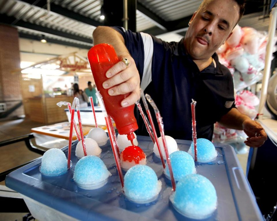 Photo -  Robert Channer prepares snow cones to be sold during a game between the Oklahoma City Redhawks and the Omaha Storm Chasers in Oklahoma City, Saturday, July 9, 2011.  The temperature in Oklahoma City reached 110.  Photo by Garett Fisbeck, The Oklahoman ORG XMIT: KOD