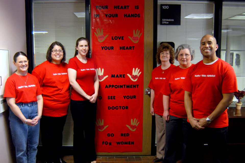 Several members of the Rose State College admissions staff stand in front of  their decorated door promoting �Go Red for Women,� during February Heart Month.<br/><b>Community Photo By:</b> Steve Reeves<br/><b>Submitted By:</b> Donna, Choctaw