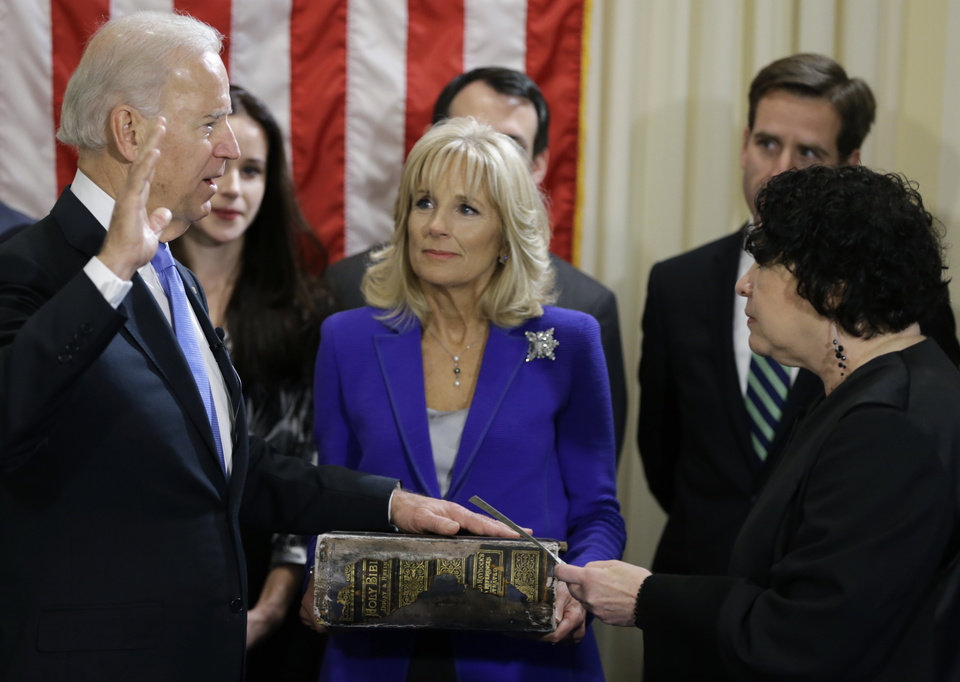 Vice President Joe Biden, with his wife Jill Biden, center, holding the Biden Family Bible, takes the oath of office from Supreme Court Justice Sonia Sotomayor during an official swearing in ceremony at the Naval Observatory, Sunday, Jan. 20, 2013, in Washington. (AP Photo/Carolyn Kaster)