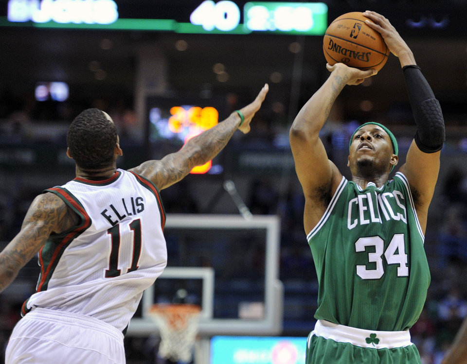 Milwaukee Bucks' Monta Ellis (11) defends as Boston Celtics' Paul Pierce (34) shoots a three-point basket during the first half of an NBA basketball game, Saturday, Nov. 10, 2012, in Milwaukee. (AP Photo/Jim Prisching)
