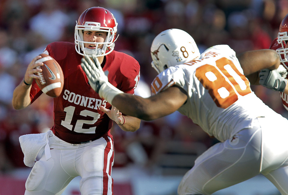 Oklahoma\'s Landry Jones (12) tries to get away from the pressure of Texas\' Alex Okafor (80) in the second half of the Red River Rivalry college football game between the University of Oklahoma Sooners (OU) and the University of Texas Longhorns (UT) at the Cotton Bowl on Saturday, Oct. 2, 2010, in Dallas, Texas. Photo by Chris Landsberger, The Oklahoman