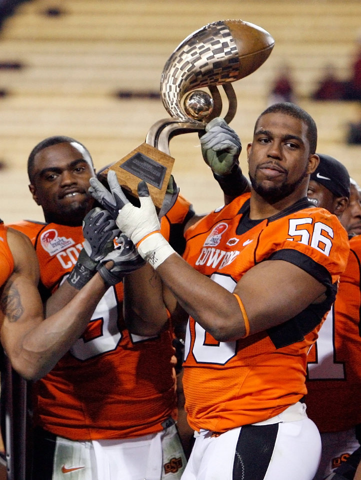 Photo - OSU's Marque Fountain (97), left, and Maurice Cummings (56) hold the Inisght Bowl trophy after the Insight Bowl college football game between Oklahoma State University (OSU) and the Indiana University Hoosiers (IU) at Sun Devil Stadium on Monday, Dec. 31, 2007, in Tempe, Ariz. OSU won, 49-33. BY NATE BILLINGS, THE OKLAHOMAN