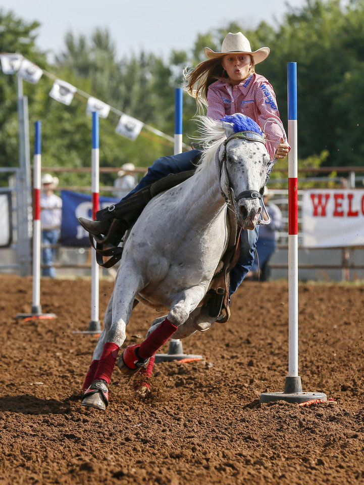Photo -  Emily Williams of Boyd, Texas, competes in pole bending on Thursday during the International Finals Youth Rodeo at the Heart of Oklahoma Exposition Center in Shawnee. [Nate Billings/The Oklahoman]