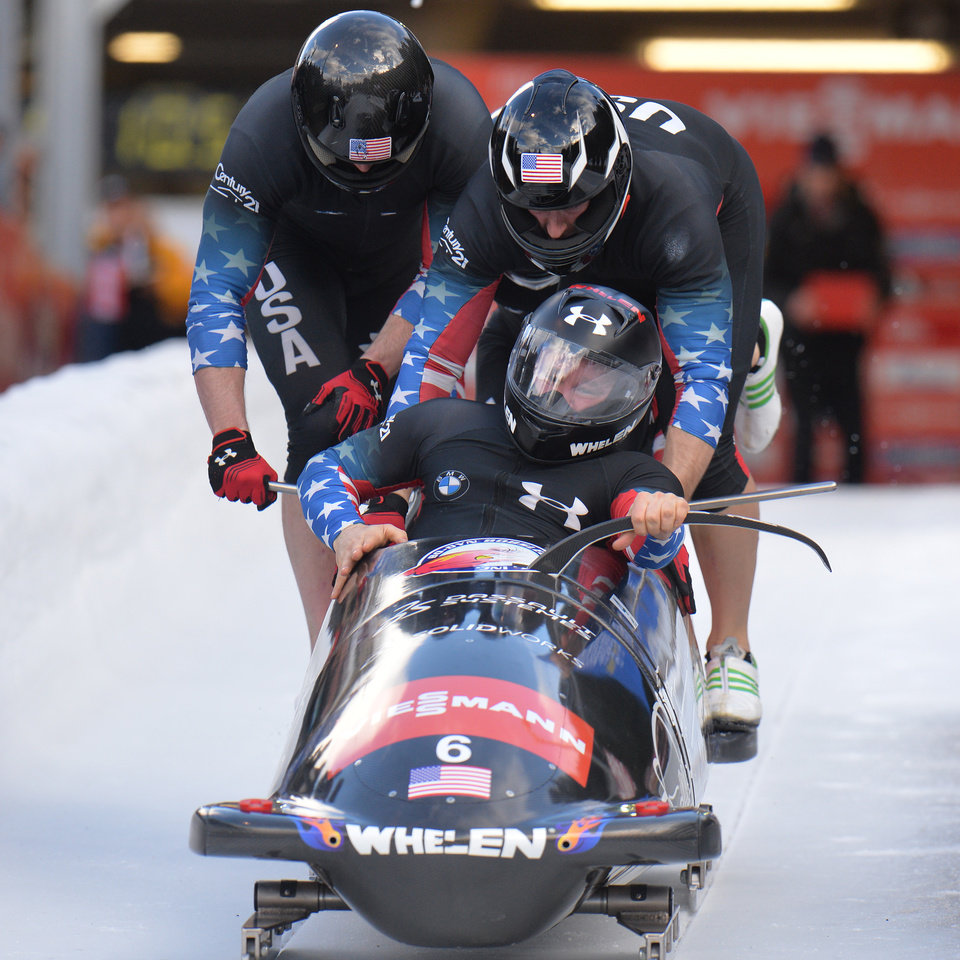 Photo - Steven Holcomb, front, of the United States leads his team during the start of the four-men Bob World Cup race in Innsbruck, Austria, Sunday, Jan. 19. 2014. (AP Photo/Kerstin Joensson)