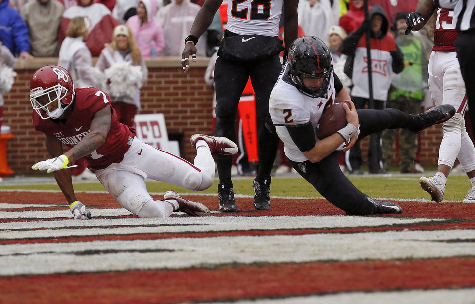 Photo - Oklahoma State's Mason Rudolph (2) scores a touchdown as Oklahoma's Jordan Thomas (7) defends during the Bedlam college football game between the Oklahoma Sooners (OU) and the Oklahoma State Cowboys (OSU) at Gaylord Family - Oklahoma Memorial Stadium in Norman, Okla., Saturday, Dec. 3, 2016. Photo by Sarah Phipps, The Oklahoman