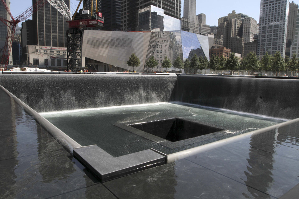 Photo - FILE - In this Aug. 17, 2011, file photo, the National September 11 Memorial and Museum is seen in the background as water flows in the south pool of the World Trade Center Memorial in New York. Twelve years after terrorists destroyed the old World Trade Center, the new World Trade Center is becoming a reality, with a museum commemorating the attacks and two office towers where thousands of people will work set to open within the next year. (AP Photo/Mary Altaffer, File)