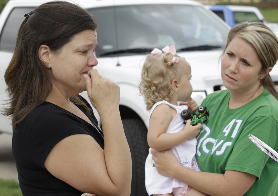 Photo -   Misty Jones, left, mother of Abigail, center, fights back emotions Wednesday, April 4, 2012, as she talks about discovering that the home of her daughter's babysitter was struck by a tornado Tuesday, in Forney, Texas. Jones' sister-in-law Jennifer Steed, right, watches as she tells of how Abigail was pulled from the rubble of the completely destroyed home. (AP Photo/Tony Gutierrez)