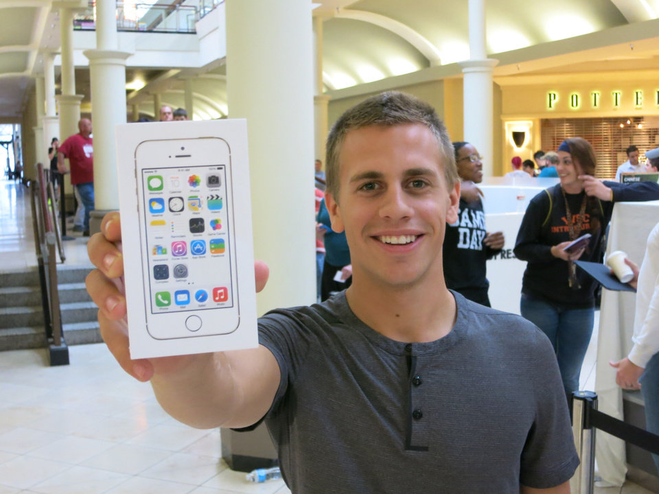 Photo - A customer shows off his new iPhone at Penn Square Mall in Oklahoma City.