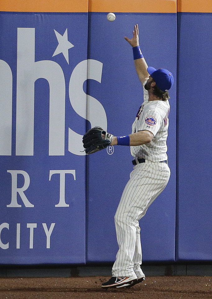 Photo - New York Mets center fielder Kirk Nieuwenhuis (9) plays the ball off the wall on a double hit by Atlanta Braves' B.J. Upton in the sixth inning of a baseball game, Wednesday, July 9, 2014, in New York. Pitcher Ervin Santana scored on the play. (AP Photo/Julie Jacobson)
