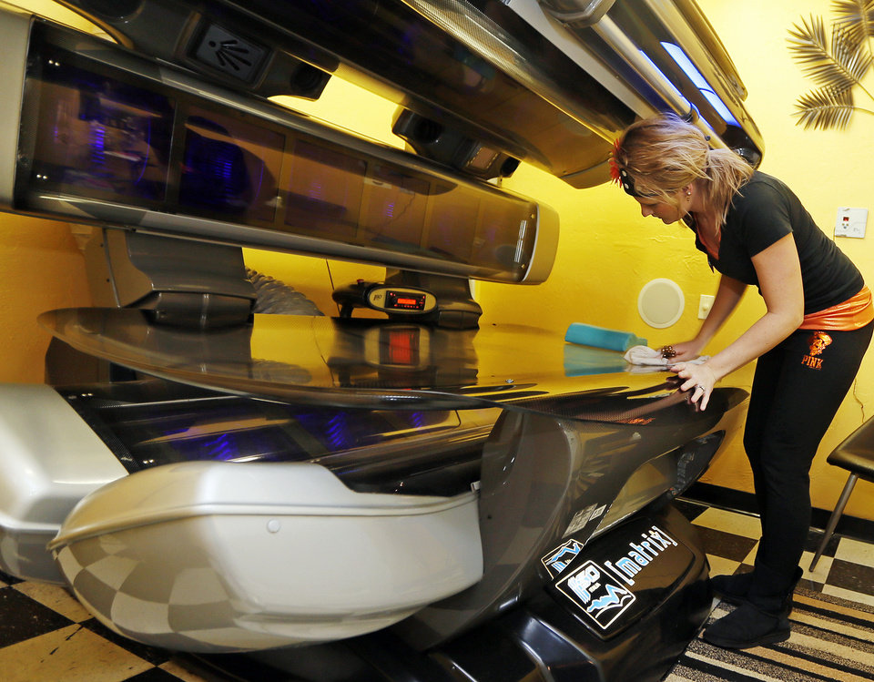 Photo - Employee Sarah Spears sanitizes a tanning bed at Tan & Tone Unlimited in Stillwater. Formerly a Tan & Tone America franchise, the business is distancing itself from the corporate chain.  NATE BILLINGS - THE OKLAHOMAN