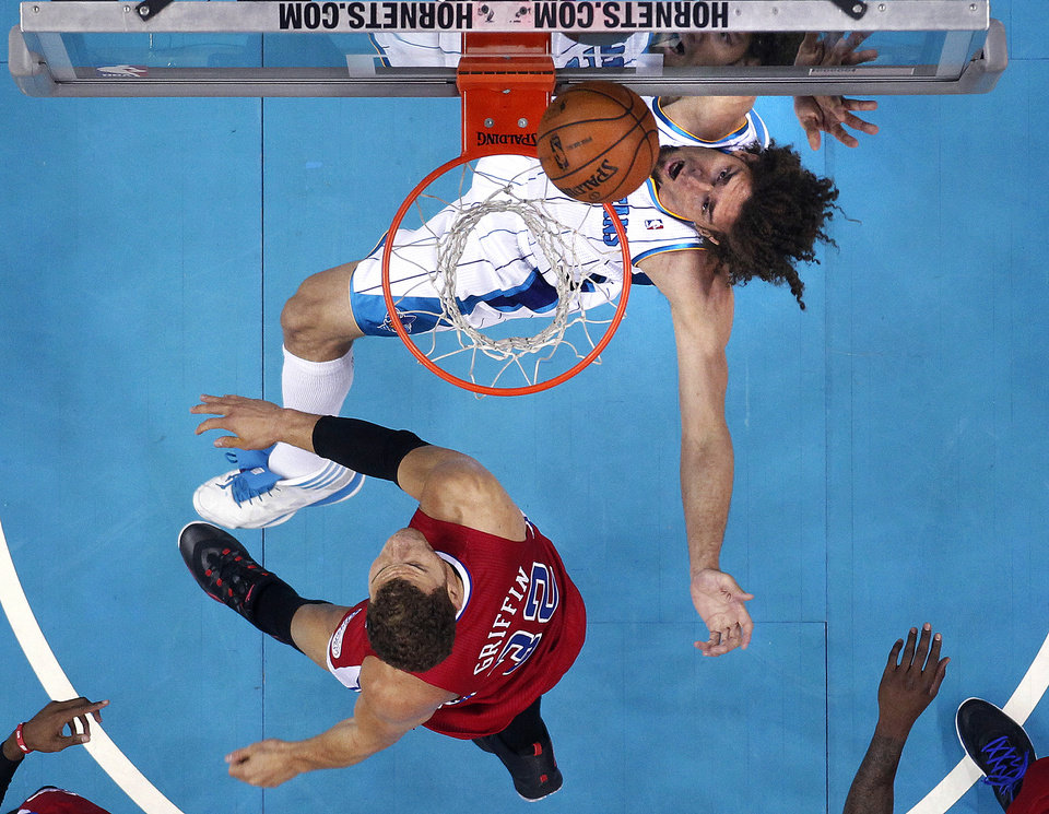 New Orleans Hornets center Robin Lopez, top, goes to the basket against Los Angeles Clippers forward Blake Griffin (32) in the first half of an NBA basketball game in New Orleans, Wednesday, March 27, 2013. (AP Photo/Gerald Herbert)