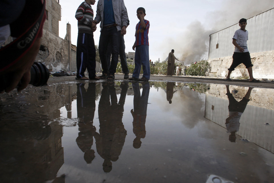 Photo -   Palestinians are reflected in a pool of water after the fire was put out in a wood factory hit in an Israeli airstrike in east Jabaliya, northern Gaza Strip, Friday, Nov. 16, 2012. (AP Photo/Hatem Moussa)