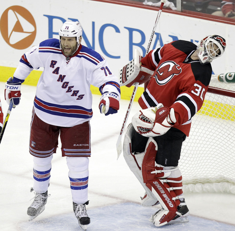 Photo -   New Jersey Devils goalie Martin Brodeur reacts after being punched by New York Rangers' Mike Rupp, center, during the third period of Game 4 of an NHL hockey Stanley Cup Eastern Conference final playoff series, Monday, May 21, 2012, in Newark, N.J. The Devils won 4-1. (AP Photo/Julio Cortez)