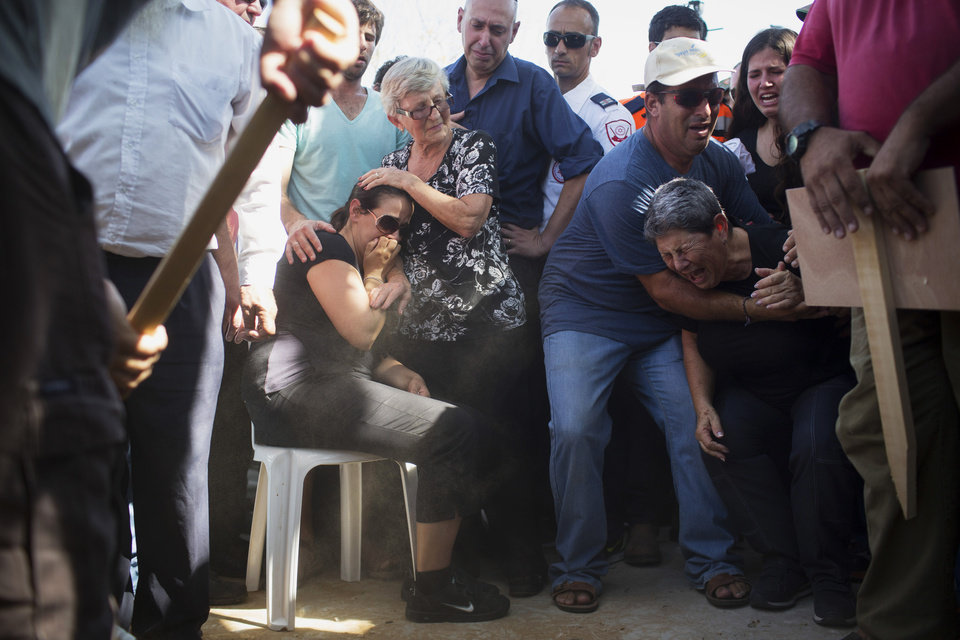 Photo - Gila, center, mother of four-year-old Israeli boy Daniel Tragerman, sits next to his grave during his funeral in a cemetery located next to the Israeli community of Yevul, near the Israeli Gaza border, Sunday, Aug. 24, 2014. Tragerman was killed when a mortar shell hit two cars in the parking lot of Nahal Oz, a small farming community near Gaza. (AP Photo/Oren Ziv)