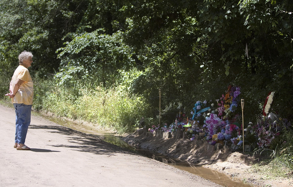 Anna Roberts of Henryetta, Okla., looks at a makeshift memorial on the side of the road, Sunday, June, 14, 2008, near the spot Taylor Paschal-Placker and Skyla Whitaker were shot last week. SARAH PHIPPS, THE OKLAHOMAN