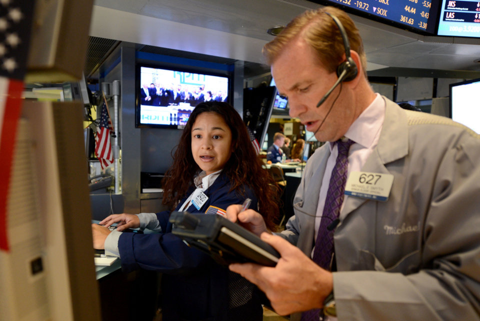 Photo -   Wingszi Chang, left, of Getco Securities, and Michael Smyth of MND Partners trade on the floor of the New York Stock Exchange Monday, July 23, 2012 in New York. The Dow Jones industrial average closed down 101.11 points to 12721.46. (AP Photo/Henny Ray Abrams)
