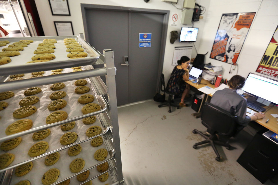 Photo - In this June 19, 2014 photo, bakery owner Julie Berliner, center, works with a colleague planning for a new kitchen, as freshly baked cannabis-infused cookies cool on a rack, at Sweet Grass Kitchen, a well-established gourmet marijuana edibles bakery which sells its confections to retail outlets, in Denver. Sweet Grass Kitchen, like other cannabis food producers in the state, is held to rigorous health inspection standards, and has received praise from inspectors, according to Berliner. (AP Photo/Brennan Linsley)