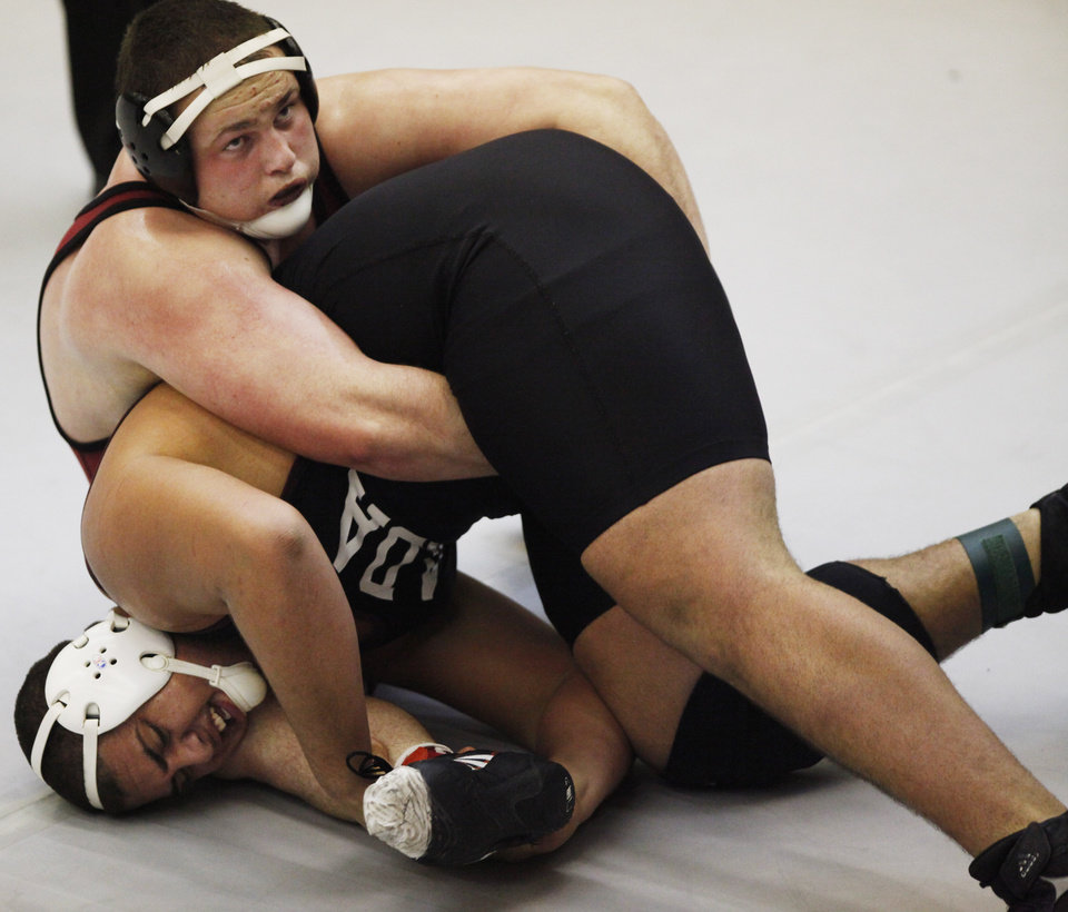 Photo - Tuttle's Dustin Mason (red) and Ada's Marwin Dickerson (black) wrestle in the 285 pound match at the 4A West Regional wrestling championship in Harrah on Saturday, Feb. 22, 2014. Tuttle's Dustin Mason defeated Ada's Marwin Dickerson to advance to state. Photo by KT King, The Oklahoman