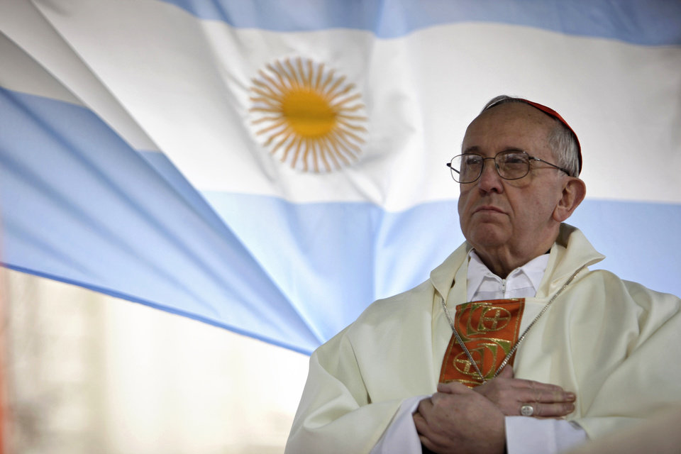 Photo - In this August 2009 photo, Argentina's Cardinal Jorge Bergoglio gives a Mass outside the San Cayetano church where an Argentine flag hangs behind in Buenos Aires, Argentina. On Wednesday, Bergoglio was elected pope, the first ever from the Americas and the first from outside Europe in more than a millennium.  Natacha Pisarenko - AP