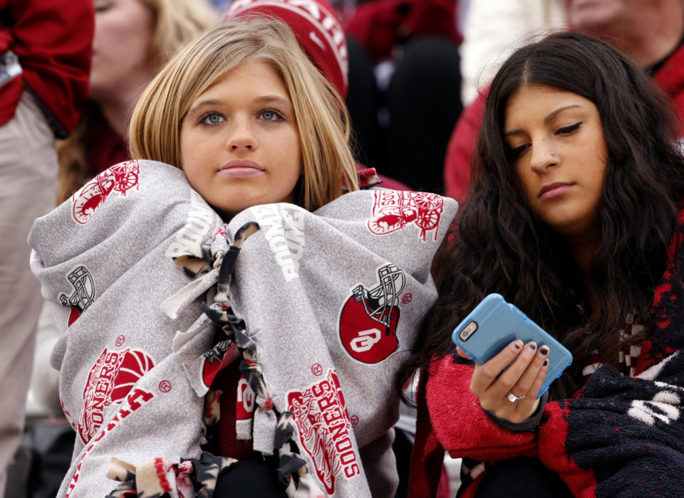 Photo - Jordan Webb and Leilah Khaled keep warm during a Bedlam college football game between the University of Oklahoma Sooners (OU) and the Oklahoma State Cowboys (OSU) at Gaylord Family-Oklahoma Memorial Stadium in Norman, Okla., on Saturday, Dec. 6, 2014. Photo by Steve Sisney, The Oklahoman