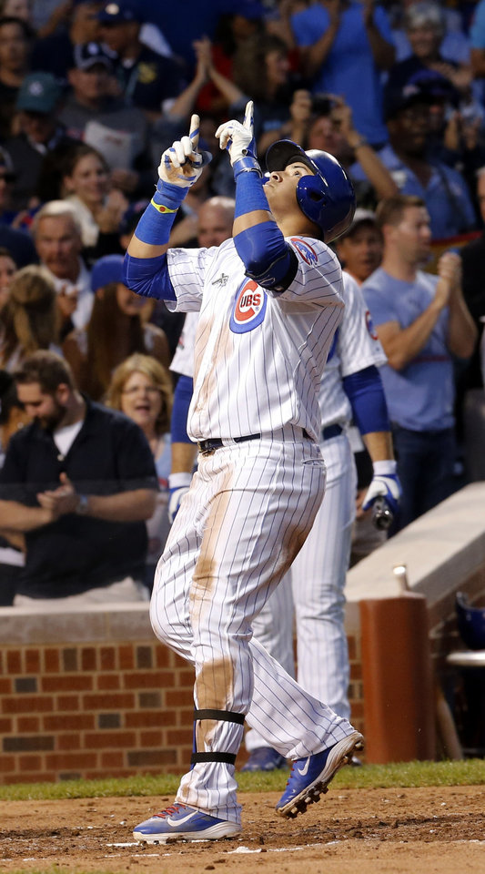 Photo - Chicago Cubs' Javier Baez celebrates at home after hitting a home run off Milwaukee Brewers starting pitcher Kyle Lohse during the third inning of a baseball game Wednesday, Aug. 13, 2014, in Chicago. (AP Photo/Stacy Thacker)
