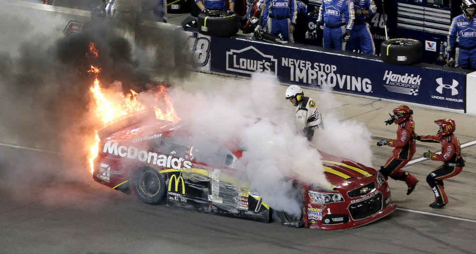 Photo - Jamie McMurray comes into pit row on fire during a NASCAR Sprint Cup Series auto race at Kansas Speedway in Kansas City, Kan., Saturday, May 10, 2014. (AP Photo/Charlie Riedel)