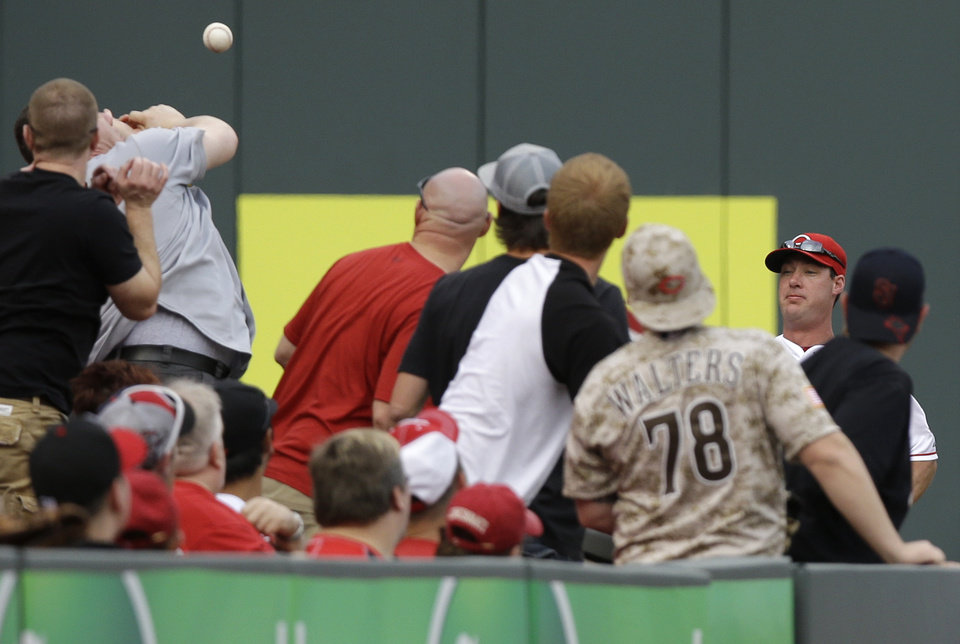 Photo - Cincinnati Reds left fielder Ryan Ludwick, right, chases a foul ball hit into the stands in the first inning of a baseball game against the St. Louis Cardinals, Saturday, May 24, 2014, in Cincinnati. (AP Photo/Al Behrman)