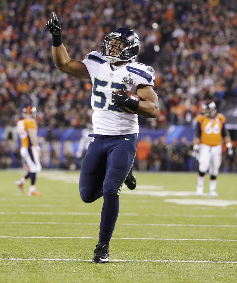 Photo - Seattle Seahawks' Malcolm Smith celebrates after scoring a touchdown on an interception during the first half of the NFL Super Bowl XLVIII football game Sunday, Feb. 2, 2014, in East Rutherford, N.J. (AP Photo/Mark Humphrey)
