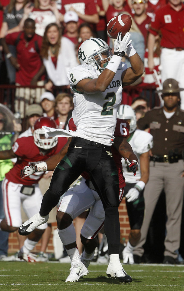 Photo -   Baylor wide receiver Terrance Williams (2) catches a pass in front of Oklahoma defensive back Demontre Hurst (6) in the first quarter of an NCAA college football game in Norman, Okla., Saturday, Nov. 10, 2012. (AP Photo/Sue Ogrocki)