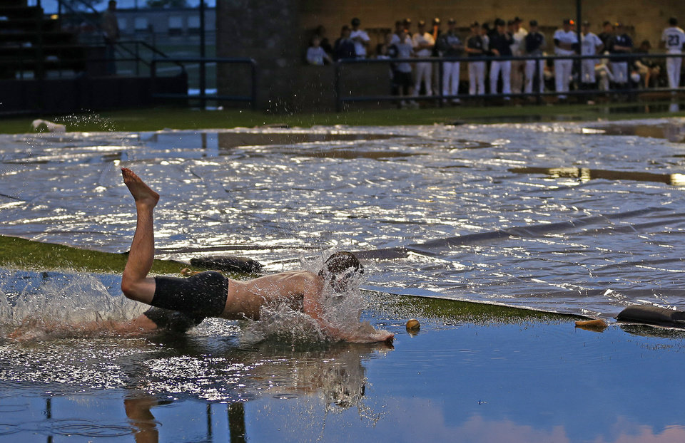 Photo - Dalton Summers of Broken Arrow dives into a puddle of water for a baseball during a weather delay before a Class 6A state baseball tournament game between Broken Arrow and Edmond North in Shawnee, Okla., Thursday, May 9, 2013. Photo by Bryan Terry, The Oklahoman