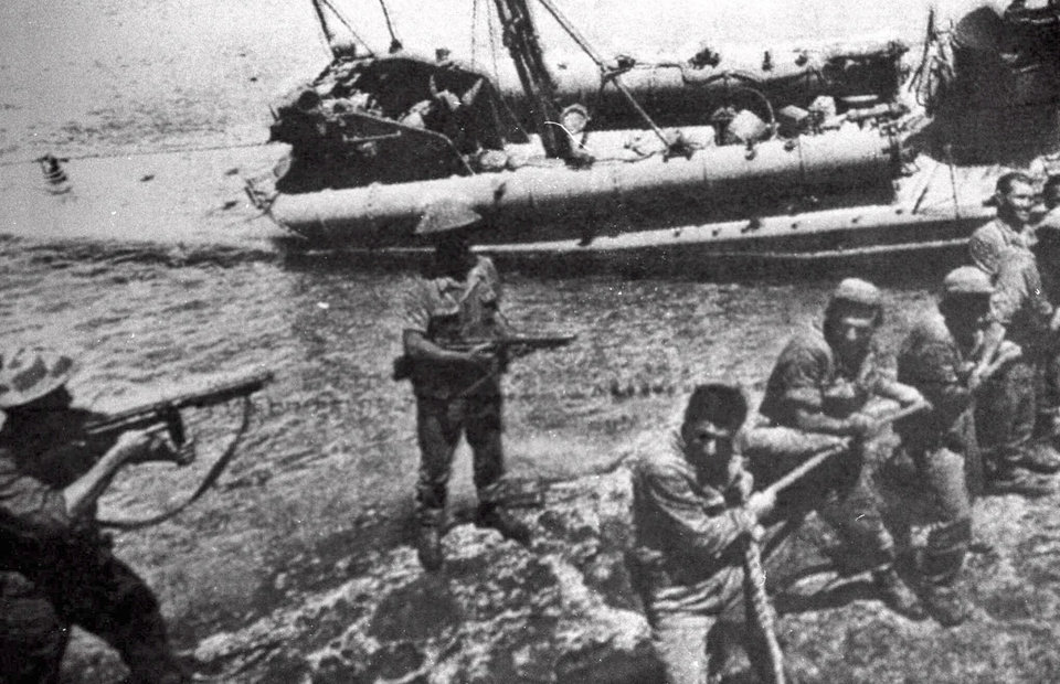 Photo - FILE- In this file photo dated July 20 1974, Turkish troops pull ashore a Greek Cypriot torpedo boat damaged during fighting in Kyrenia on the day Turkey invaded and occupied the northern third of Cyprus.  Europe's top human rights court on Monday May 12, 2014, ordered Turkey to pay 90 million euros ($123 million) to Cyprus over the 1974 invasion of the island and its subsequent division, in one of the largest judgments in its history, saying that the passage of time did not erase responsibility in the case. The judgment comes as the Turkish and Greek Cypriot communities are engaged in renewed efforts to reunite the island.(AP Photo, FILE)