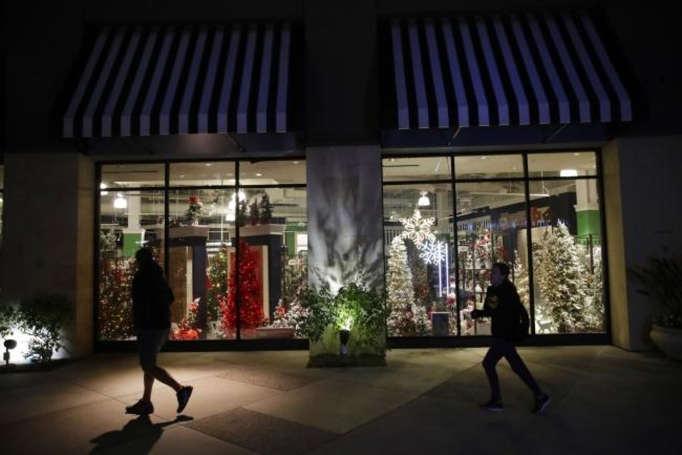Photo -  Shoppers walk past a storefront with seasonal holiday products Dec. 16, 2019, in Santa Clarita, Calif.  Whether you're trying to save, pay down debt or replenish money lost due to pandemic-related setbacks, you can stay true to your financial goals by borrowing tips from minimalists. [AP File Photo/Marcio Jose Sanchez]