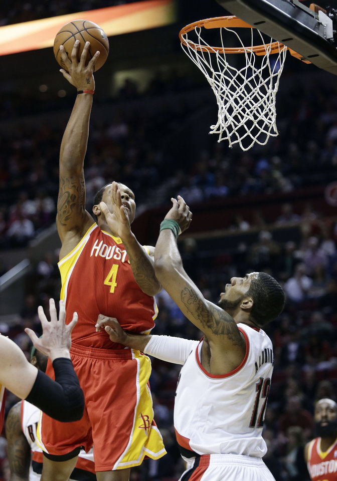 Houston Rockets forward Greg Smith, left, shoots over Portland Trail Blazers forward LaMarcus Aldridge during the first quarter of an NBA basketball game in Portland, Ore., Friday, April 5, 2013. (AP Photo/Don Ryan)