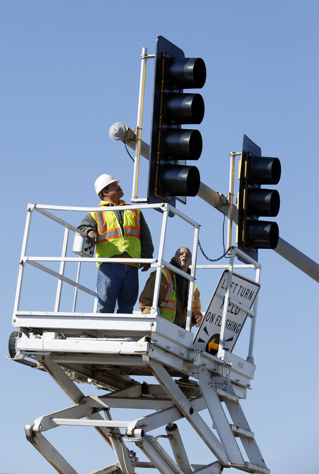 Workers with Traffic Systems Inc. install a new traffic signal at Robinson Street and Berry Road in Norman.