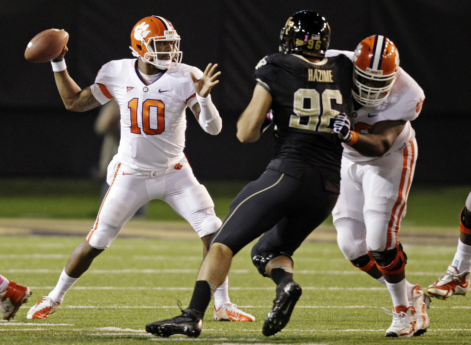 Photo -   Clemson's Tajh Boyd (10) throws a pass under pressure from Wake Forest's Hasan Hazime (96) during the first half of an NCAA college football game in Winston-Salem, N.C., Thursday, Oct. 25, 2012. (AP Photo/Chuck Burton)